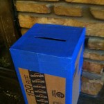 slot in the top of our cardboard mailbox, reinforced with blue painters' tape.